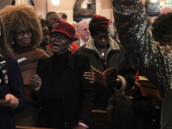 """Attendees rose to their feet for the choir's closing song, """"We Shall Overcome."""" Sheila Cooper (left) said she was moved by the event. """"It was very spiritual to see so many different races together, holding hands,"""" said Cooper, 60. """"That's what the world is about."""""""