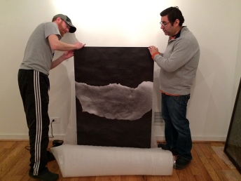 "Tommy and Doug unwrap and prepare to hang Nicole White's piece ""A Thousand Plateaus."" As the show's emerging artist, White has one piece featured in the show, which they are displaying on the back wall of the gallery. ""My work is primarily about how we see and understand photographs,"" White says. ""My work always takes a different form. Continuity is not a thing."""