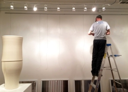 "Doug installs a wire tracking system on one of the gallery's walls a few days before the show's opening. The Ravenswood gallery features three artists — two mid-level and one emerging — every six weeks or so, each on a separate wall. The 600-square-foot modernist gallery follows the 1950s Clement Greenberg definition of modernism: ""The essence of Modernism lies, as I see it, in the use of characteristic methods of a discipline to criticize the discipline itself, not in order to subvert it but in order to entrench it more firmly in its area of competence."""
