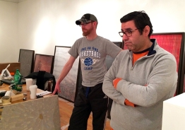 "Tommy and Doug, both artists, examine a line up of Jennifer Murray's series ""Home"", trying to determine an order for the seven pieces. ""I try to make sure there's something for everyone,"" Tommy says. ""People are intimidated by galleries. With a gallery at this level, you really have to believe in the gallerists taste."" Doug specializes in ceramics while Tommy works mainly with photography."
