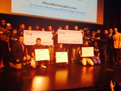 Students at Marie Curie High School pose with giant checks representing scholarships from Ford Motor Co.'s Driving Dreams Tour.