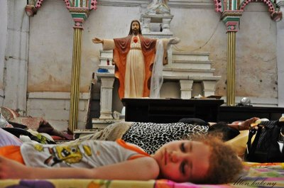 An internally displaced child sleeps on the floor of Saint Joseph's church in Arbil, Iraq. Photo by Allen Kakony/A Demand For Action