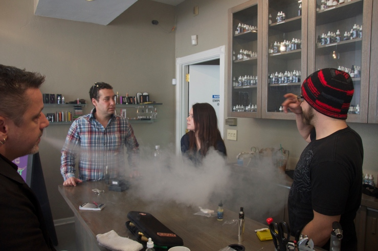 Jared Yucht, (left-center) owner of Smoque Vapours, with employees Stephanie Bowman and Michael Haynes. Frequent customer Scott Norris (far left) takes a drag from a modified vaporizer. Michael Epstein/MEDILL
